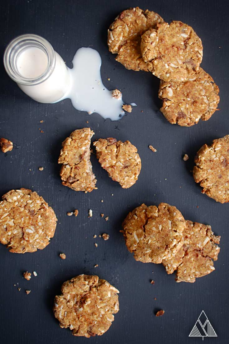 Almond flour cookies and a bottle of milk on black background