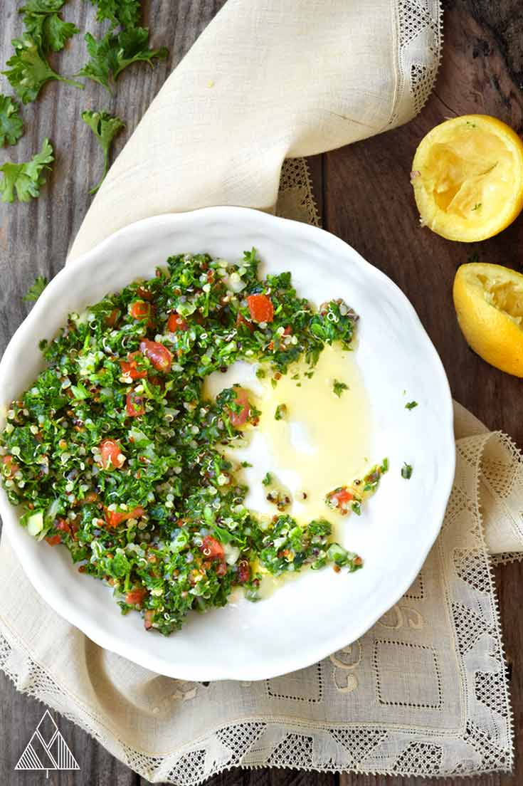 Bowl of tabouleh salad recipe on a napkin with lemons