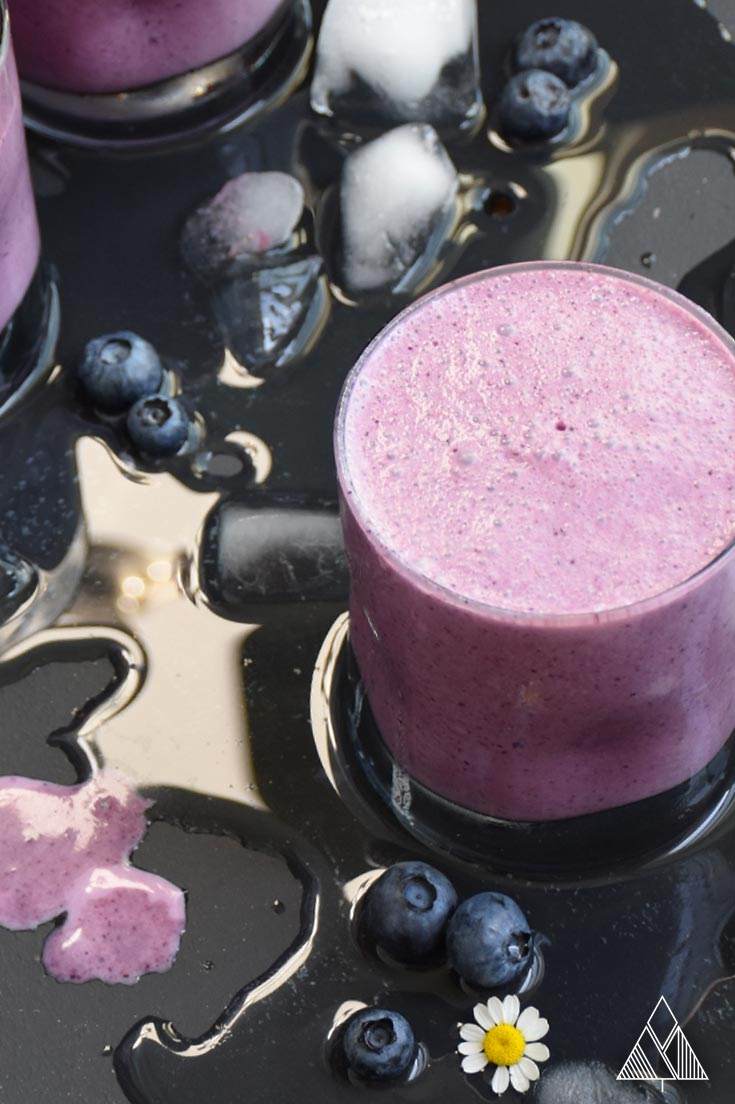 1 glass of a healthy blueberry smoothie on a black background with melted ice, blueberries and flowers