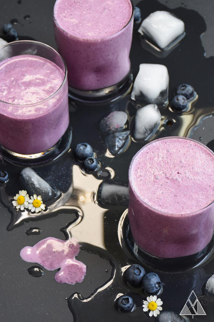 3 glasses of a healthy blueberry smoothie on a black background with melted ice, blueberries and flowers