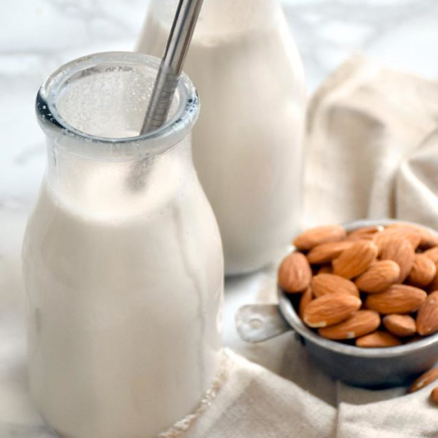 All the ingredients for how to make almond milk, plus two glasses of homemade almond milk