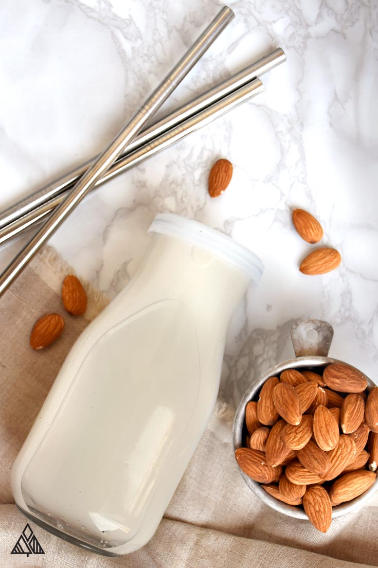 All the ingredients for how to make almond milk, plus a glass of homemade almond milk