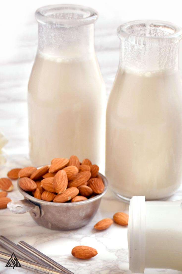 All the ingredients for how to make almond milk, plus three glasses of homemade almond milk