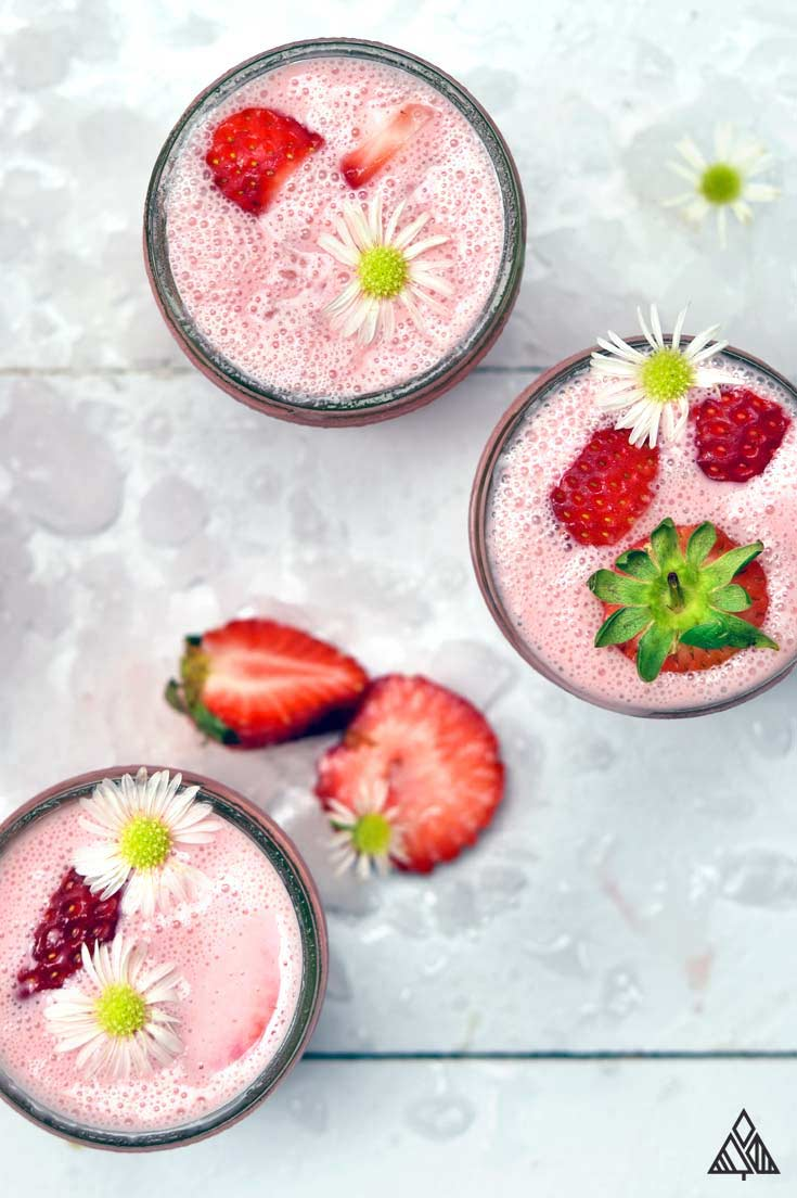 3 glasses of strawberry smoothies topped with strawberries