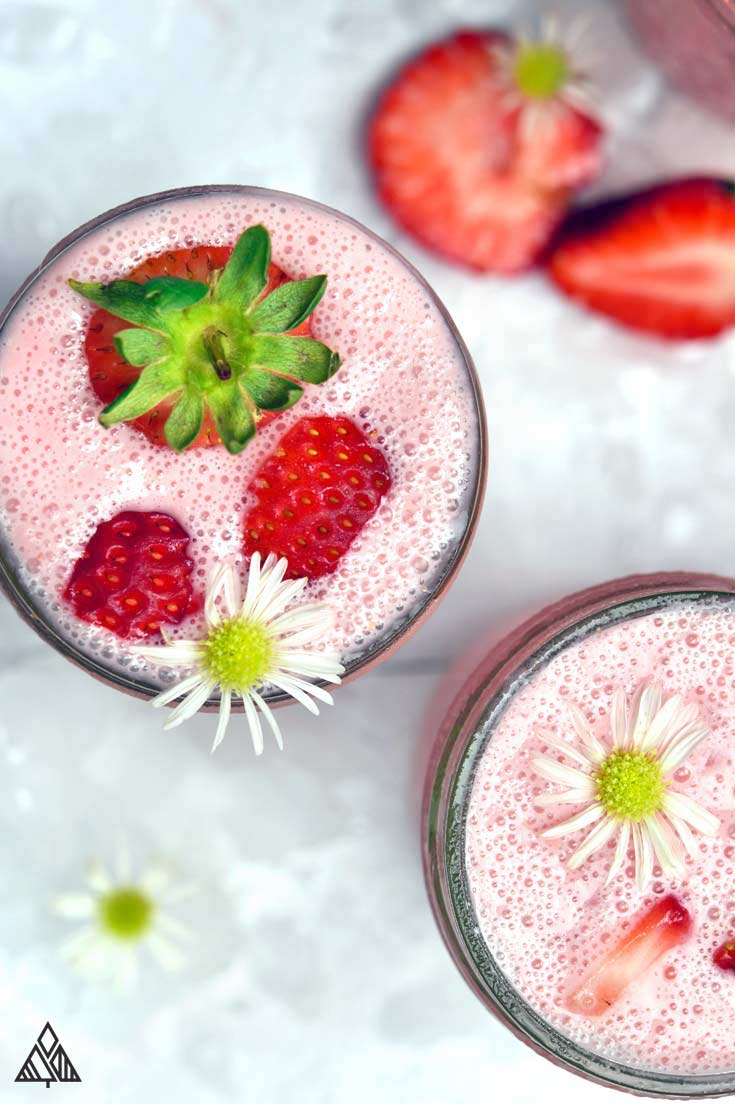 2 glasses of strawberry smoothies topped with strawberries