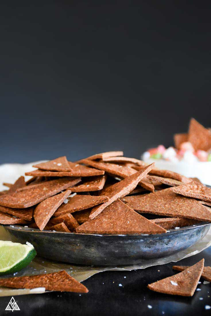 side view of low carb tortilla chips in a small black plate with black background