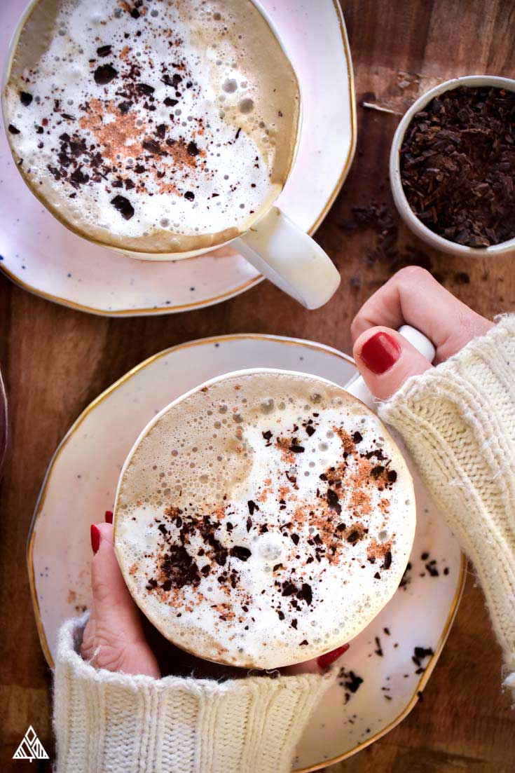 2 cups of hot chocolate with hands holding 1 cup