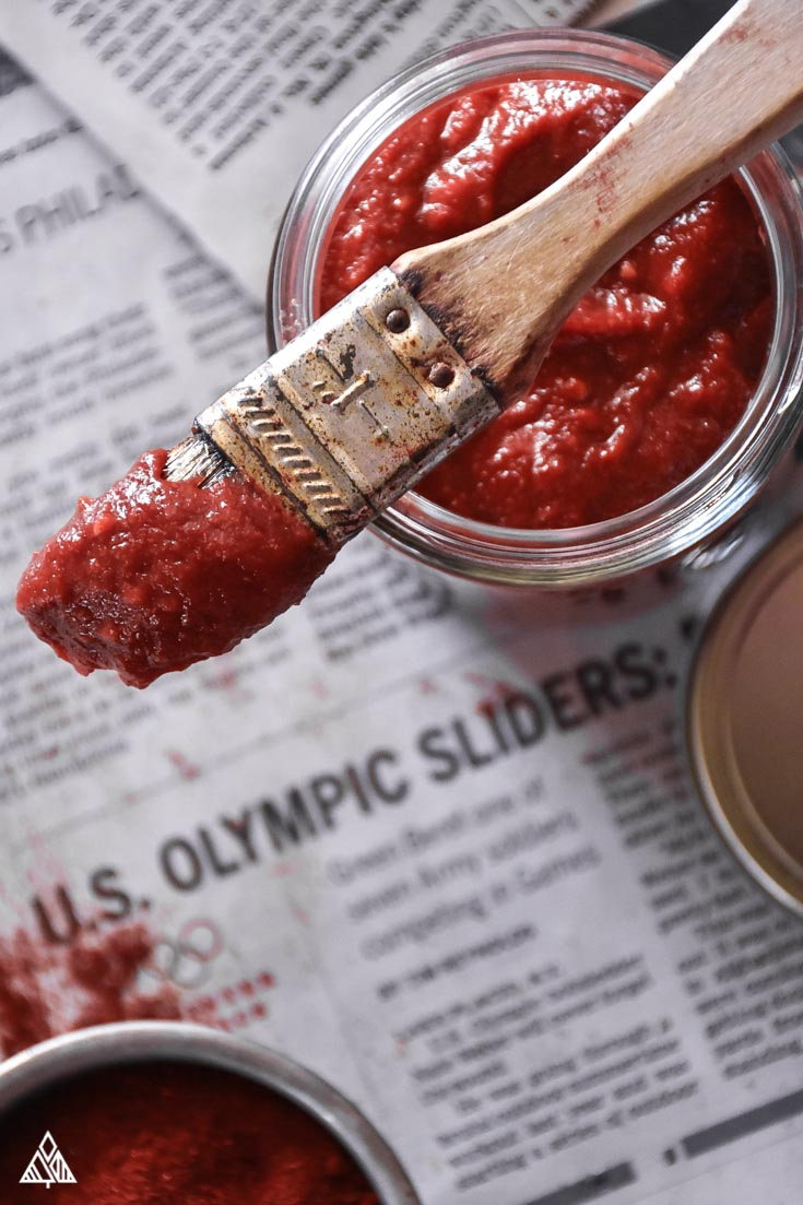 Low Carb BBQ Sauce with a brush on newspaper from overhead