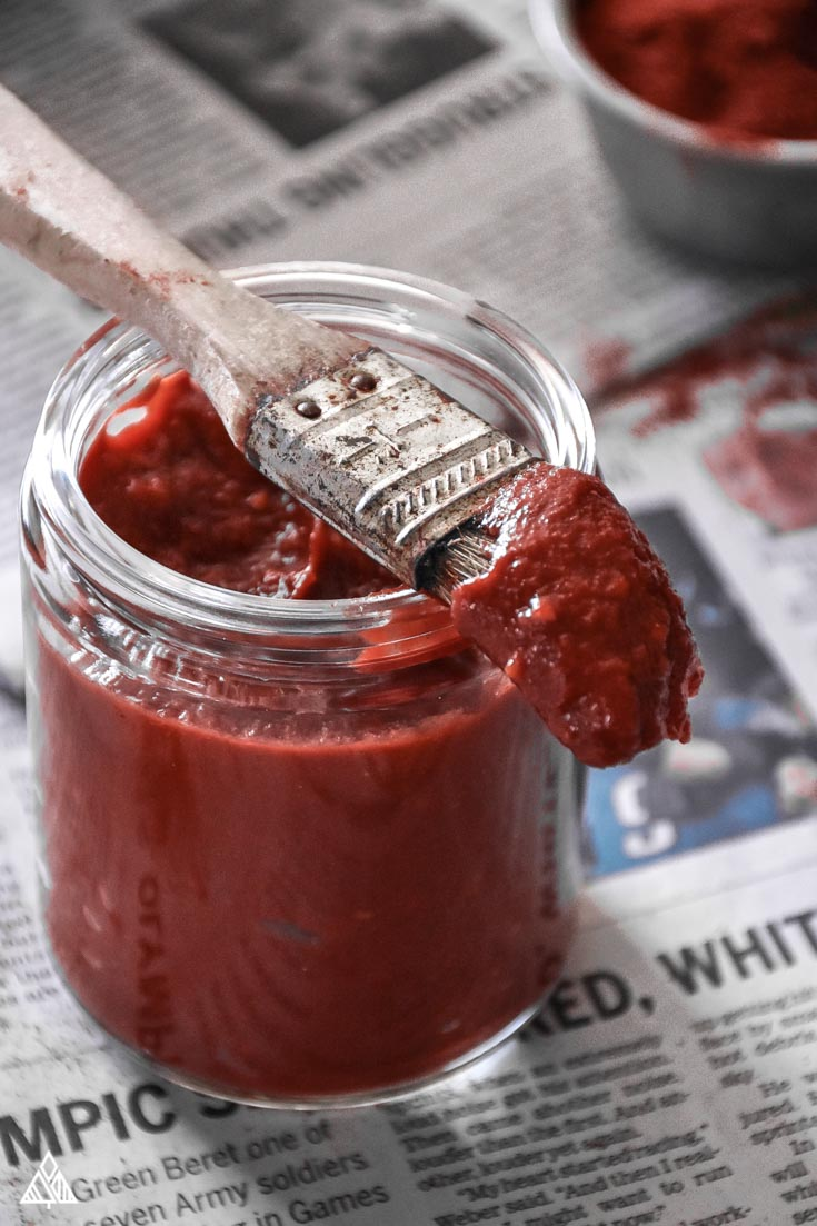 Low Carb BBQ Sauce with a brush on newspaper with spices in background
