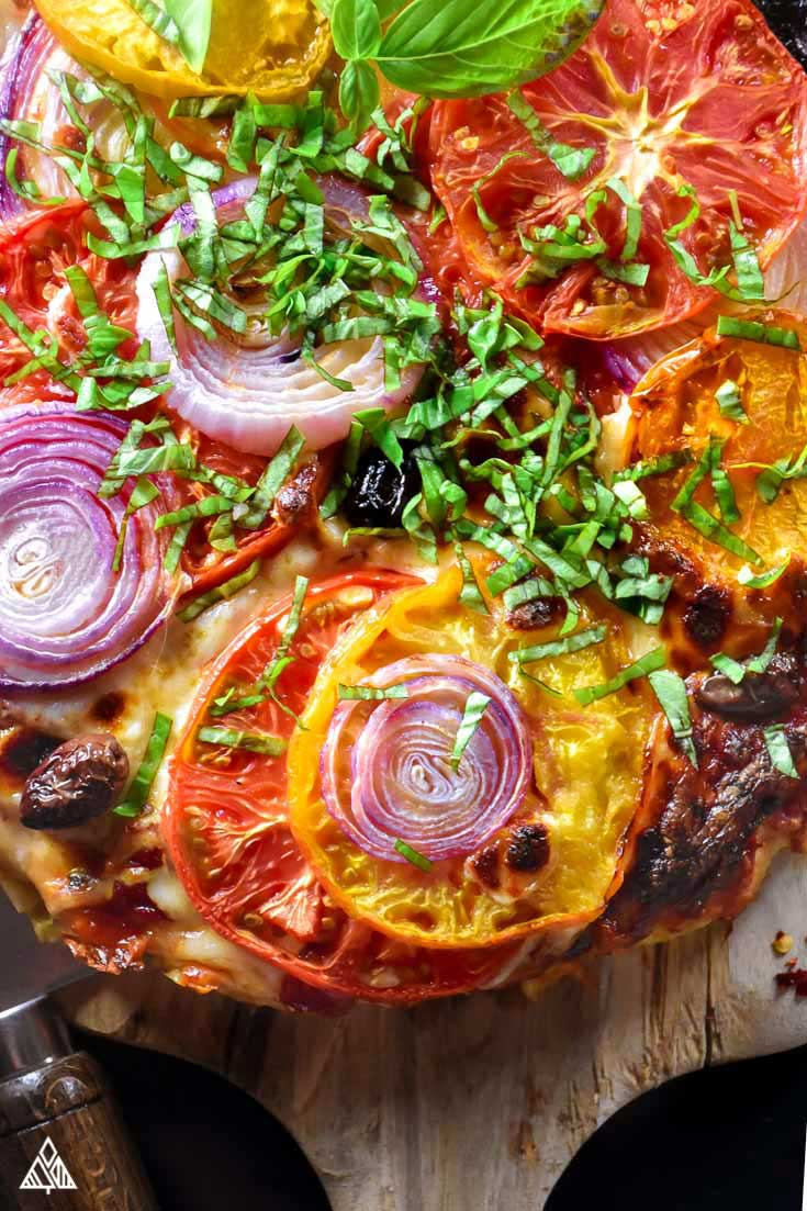 meatza topped with tomato onion and other veggies