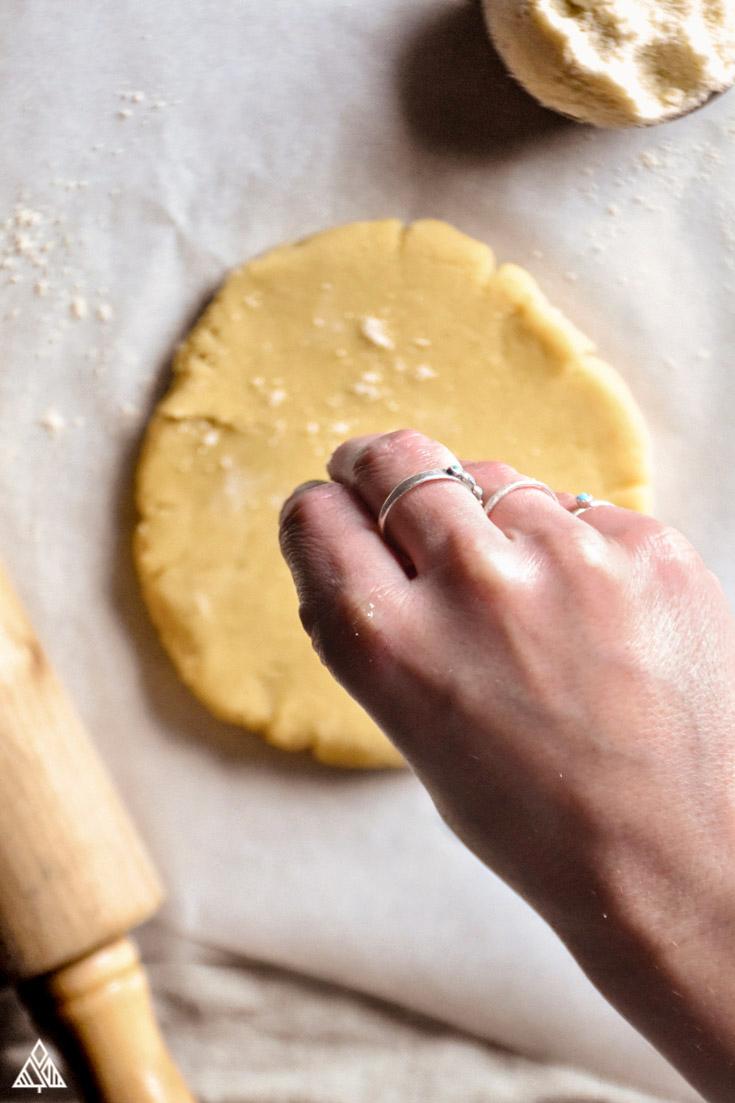 Low Carb Pie Crust dough, and a hand sprinkling low carb flour onto the dough