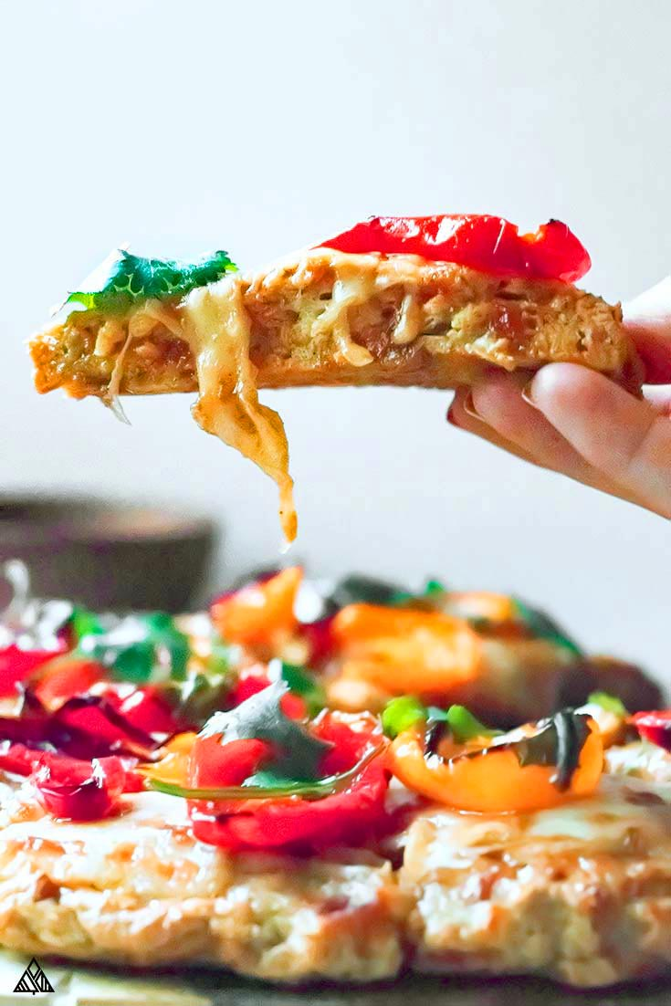 Hand holding a piece of slice of chicken crust pizza