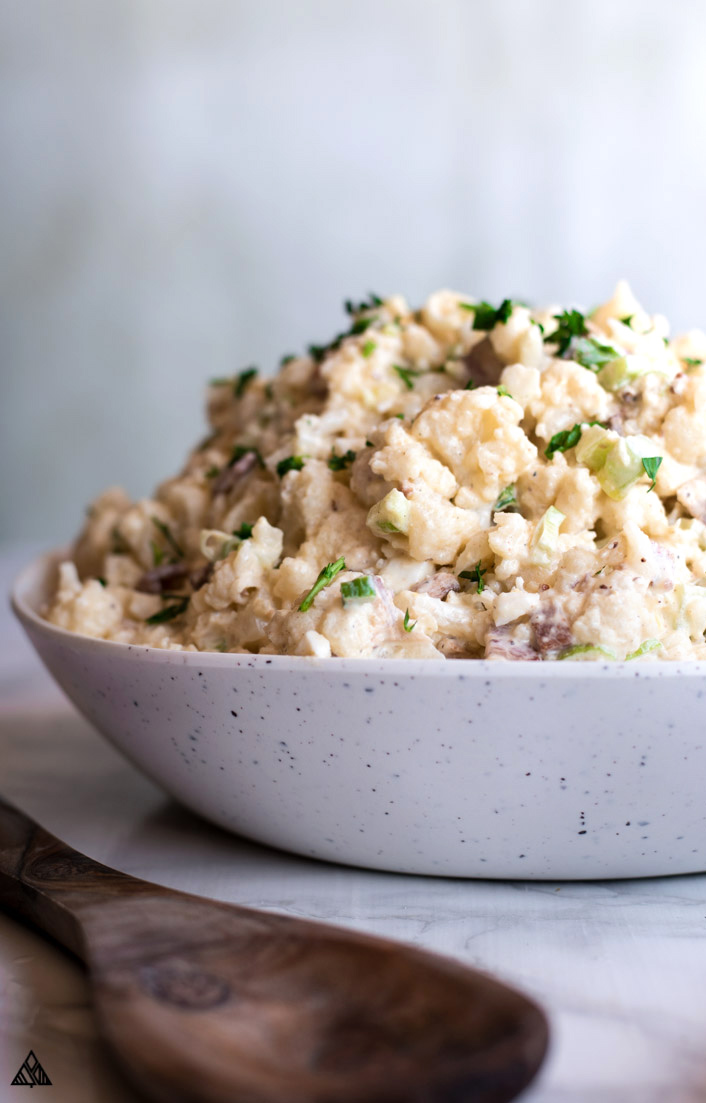 Cauliflower Potato Salad in a bowl with a spoon in front