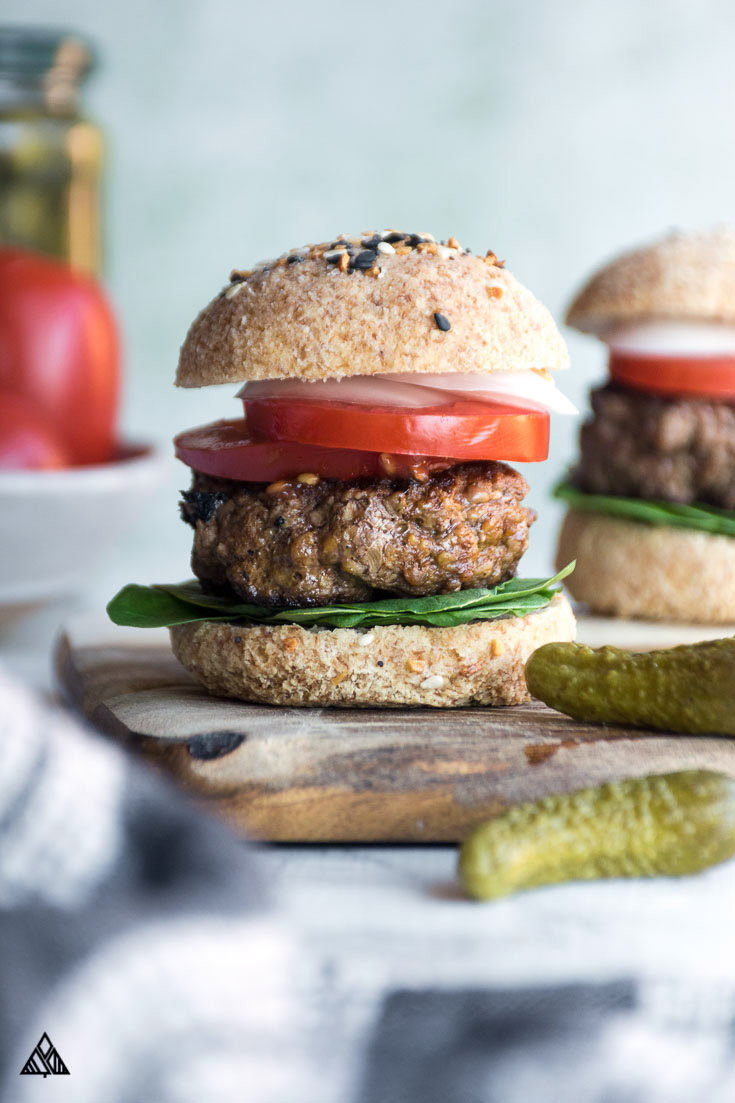 Low carb hamburger buns on a cutting board with ingredients on the side, sliced tomato, patty and other ingredients at the center