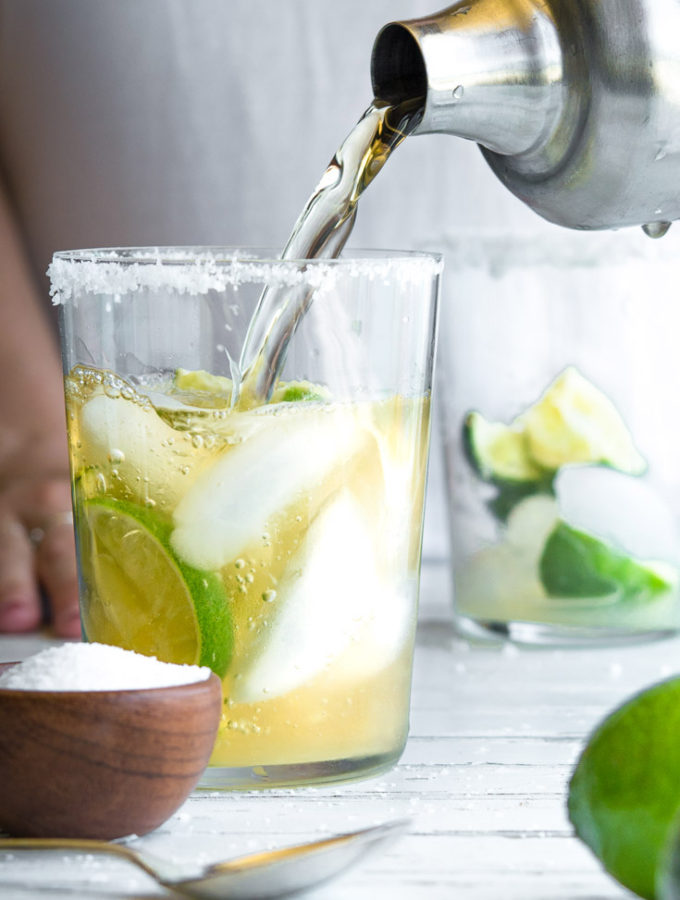 person pouring water in a glass with lime and ice