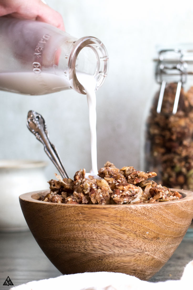 Person pouring milk in a bowl of low carb granola
