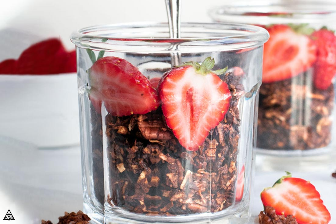 Side view of low carb chocolate granola in a glass with sliced strawberries