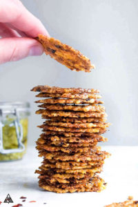 stack of Pesto Parmesan Chips with a hand holding one