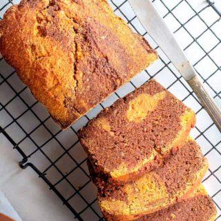 Sliced loaf of gluten free pumpkin bread on a baking tray