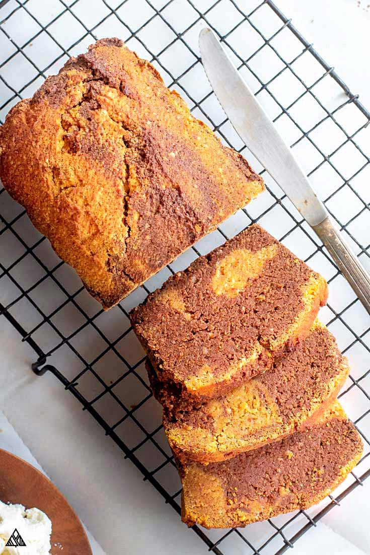 Sliced loaf of gluten free pumpkin bread with a knife on the side on a baking tray