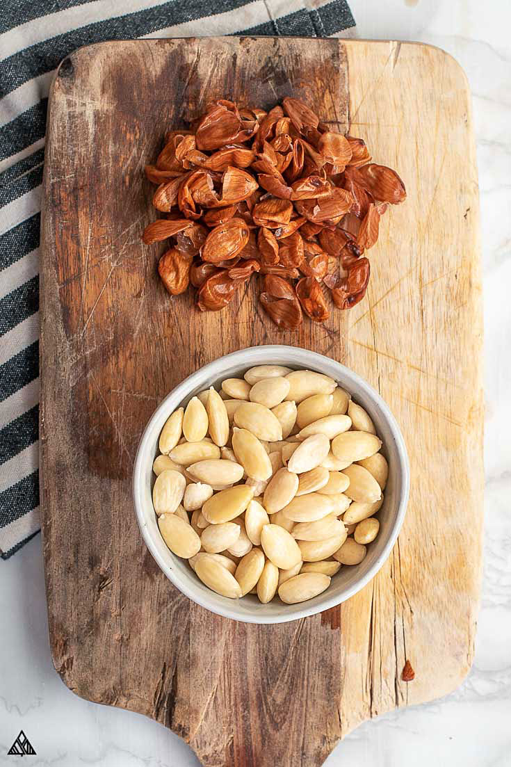 A cup of blanched almonds with the almond skin on the side