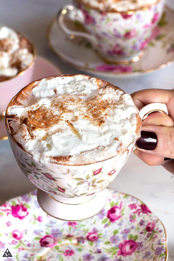 A hand holding a cup of keto hot chocolate