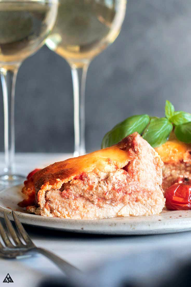Lasagna stuffed chicken topped with fresh basil and tomatoes with 2 glasses of wine on the side