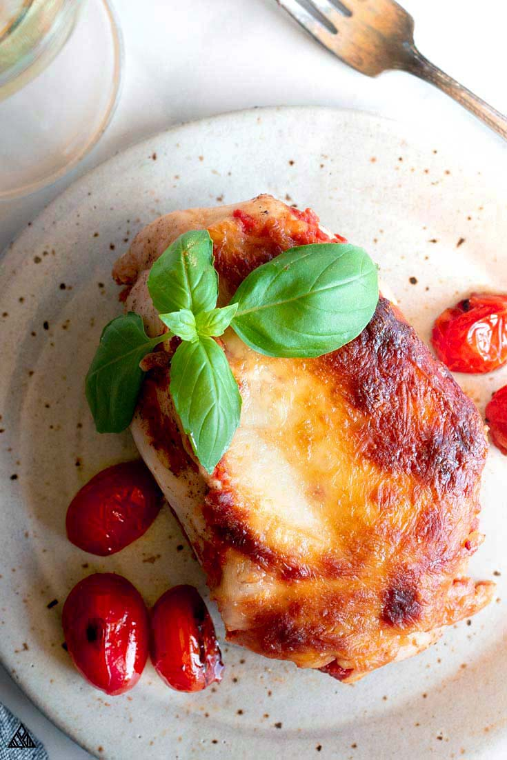 Lasagna stuffed chicken topped with fresh basil and tomatoes