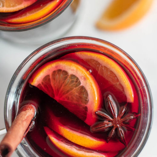 Top view of a glass of mulled wine topped with slices of lemons