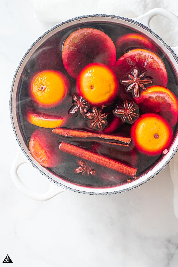 Top view of a glass of mulled wine topped with lemons