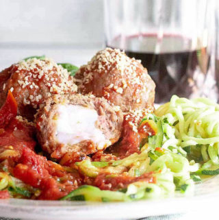 3 mozzarella stuffed meatballs on top of the veggies with wine on the background