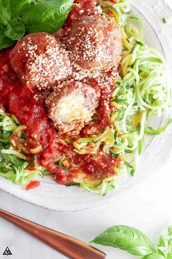 3 mozzarella stuffed meatballs on top of the veggies
