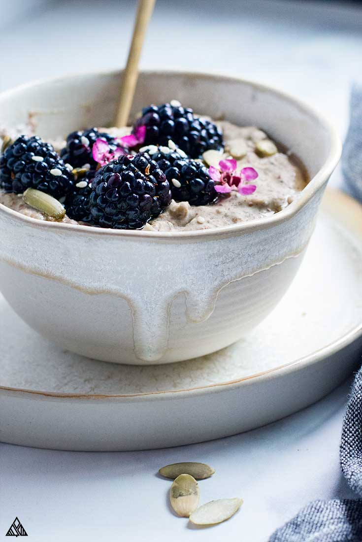 low carb oatmeal in a small bowl topped with blackberries