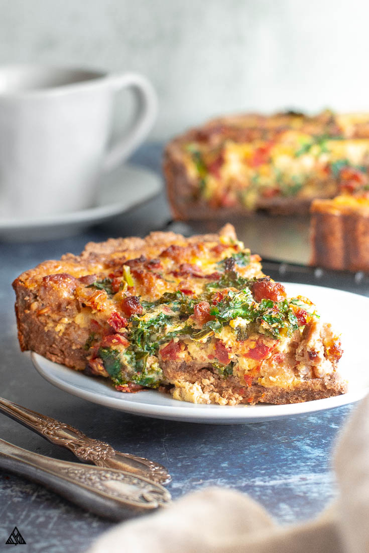 Side view of a slice of kale quiche in a white plate