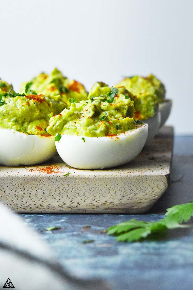 Side view of avocado deviled eggs on a cutting board