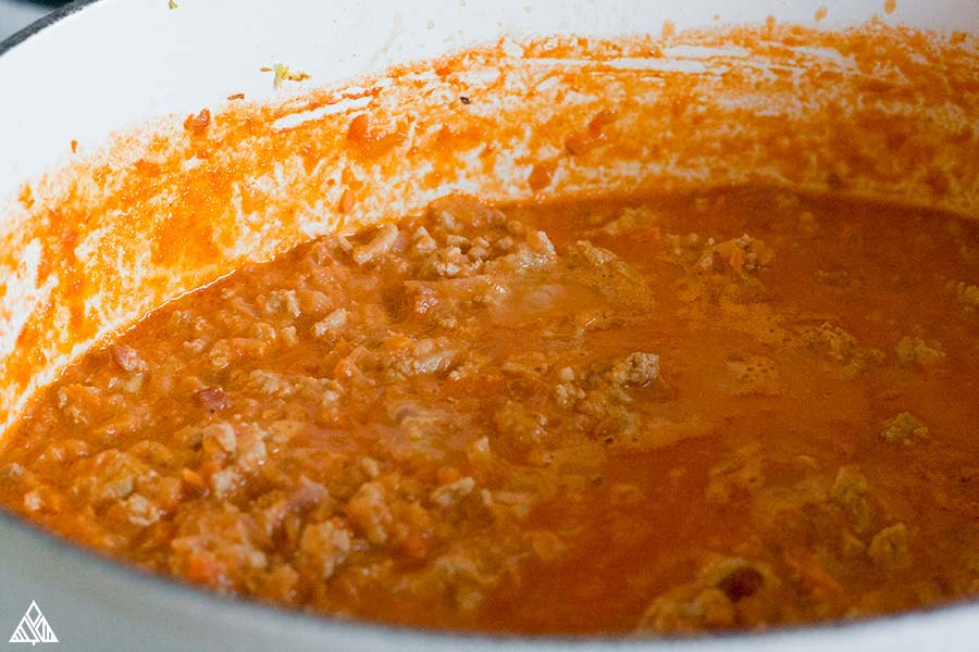 Cooked chicken bolognese in a sauce pan