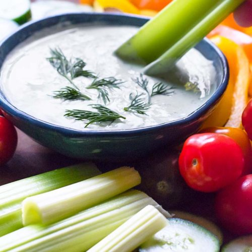 Side view of a bowl of veggie dip with chopped veggies around it