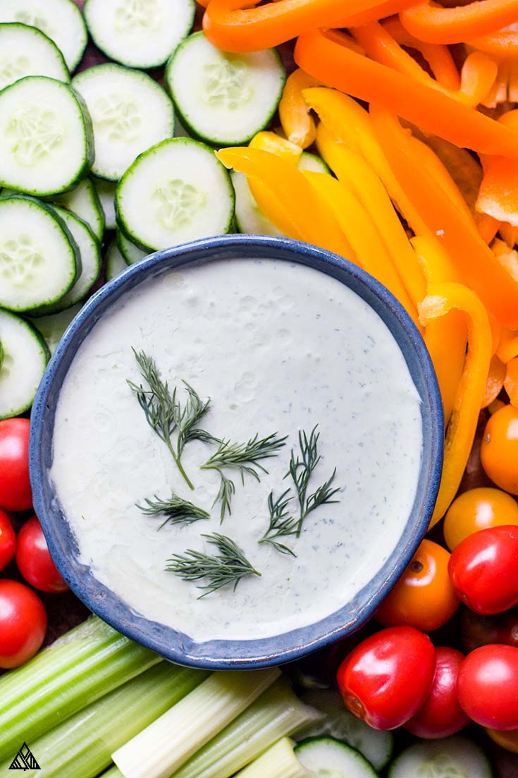 Top view of a bowl of veggie dip with chopped veggies around it