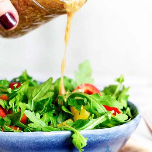 Pouring the mustard vinaigrette in to a bowl of vegetables