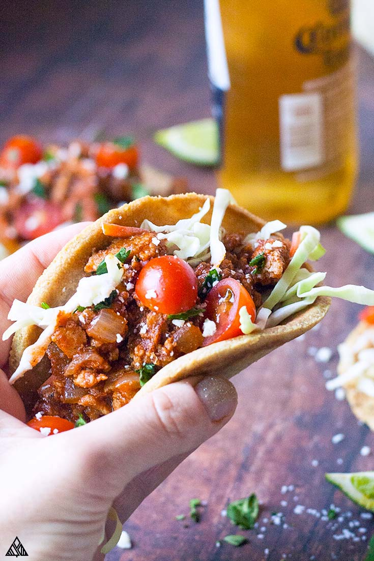 Hand holding a serfving of ground chicken tacos