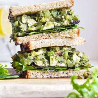 Pile of bread with avocado chicken salad in between each bread