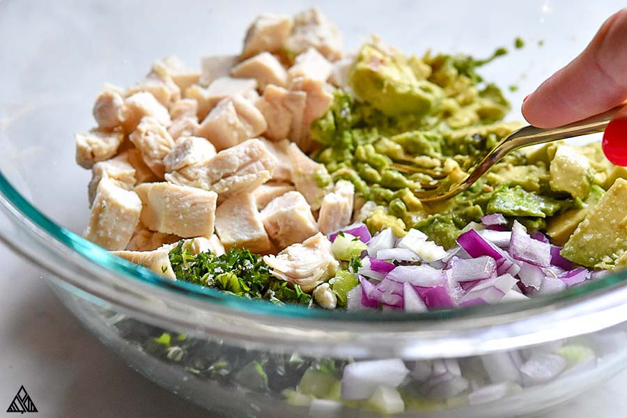 A bowl of all the ingredients for avocado chicken salad