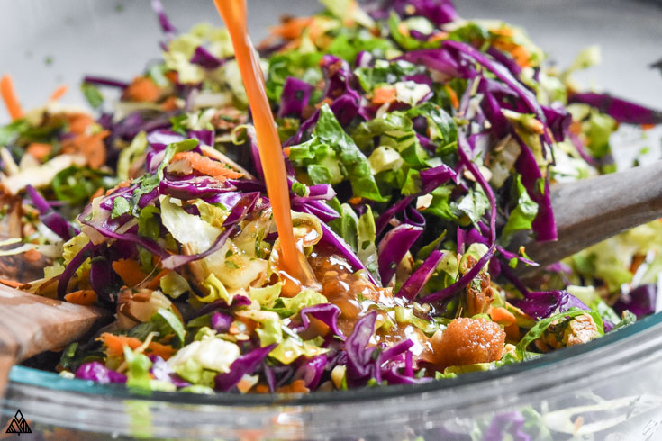 Mixing the ingredients for chinese chicken salad in a bowl