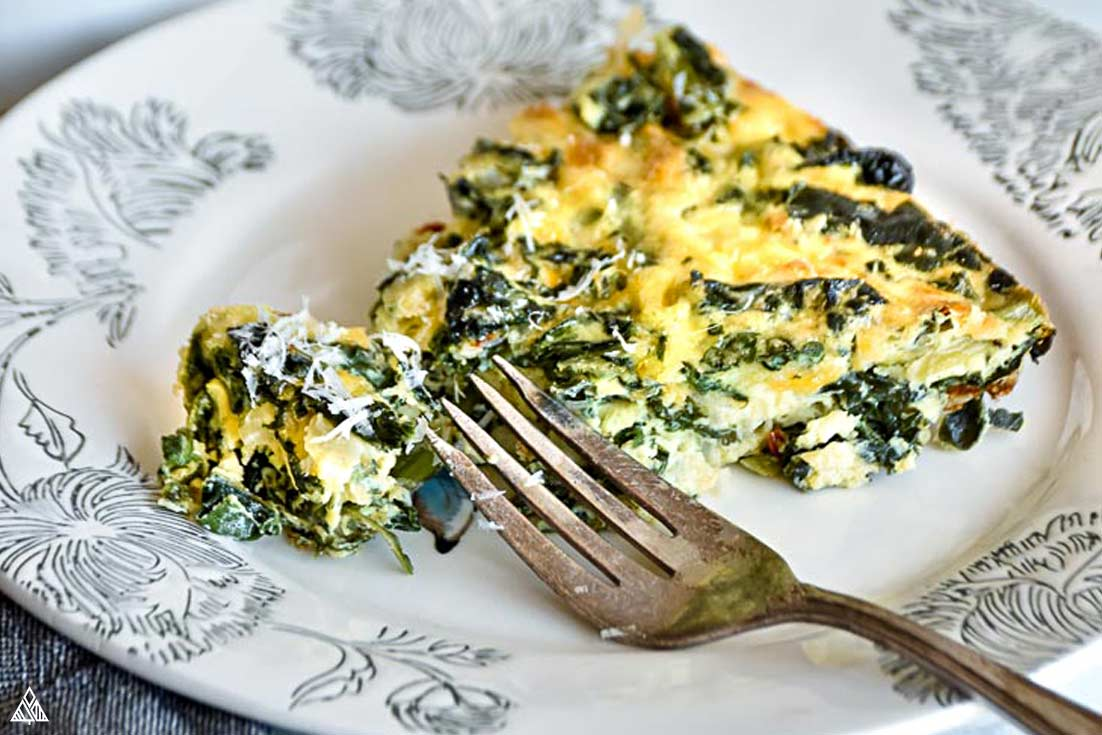 A slice of crustless quiche in a plate with a fork
