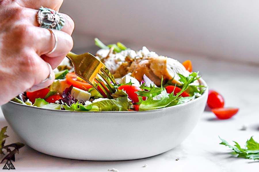 Greek chicken salad in a bowl with a hand holding a fork