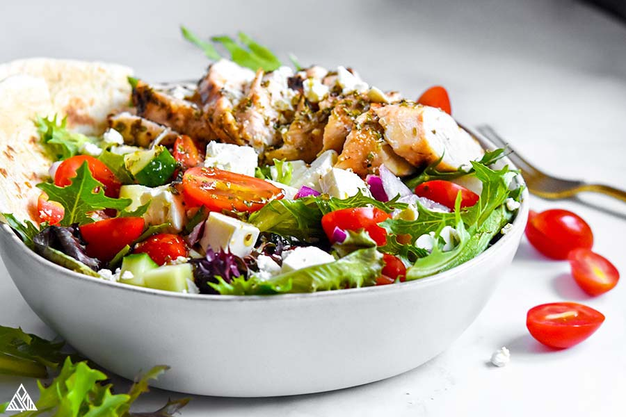 Side view of greek chicken salad in a bowl