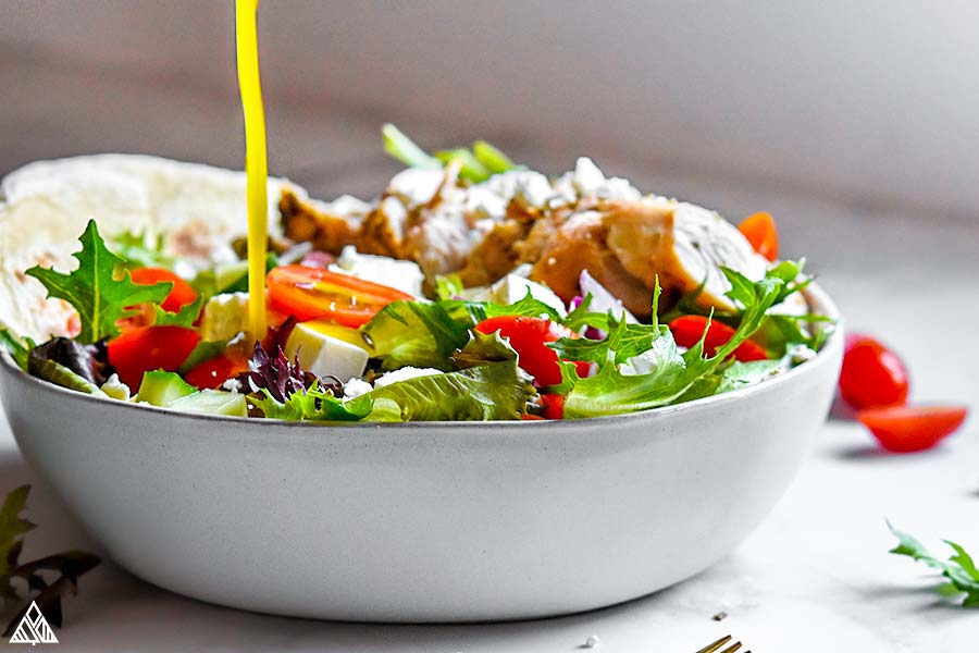 Pouring sauce in to a bowl of greek chicken salad