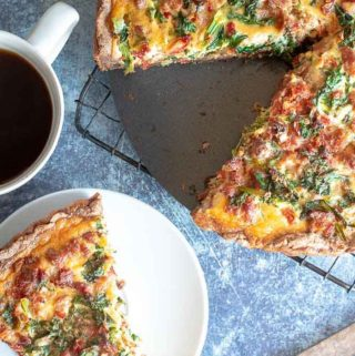 A slice of kale quiche in a small plate and a cup of coffee on the side