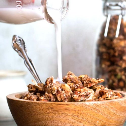 Pouring milk into a bowl of low carb granola