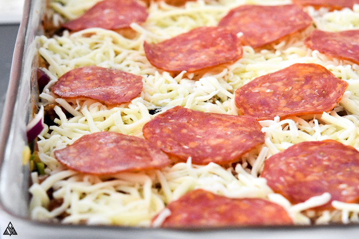 Layer of cheese and pepperonis in a casserole dish
